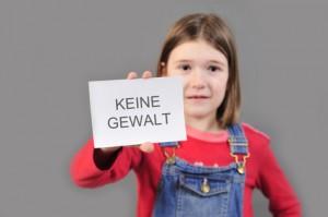 """Mädchen hält Schild mit der Aufschrift """"Keine Gewalt"""""""